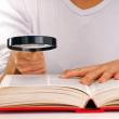 Young woman holding a magnifying glass reading a book. — Stock Photo #25379925