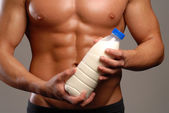 Shaped and healthy body man holding a milk bottle. — Stock Photo