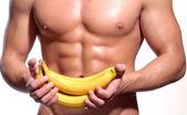 Shaped and healthy body man holding a fresh bananas — Stock Photo