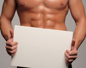 Shaped and healthy body man holding a white panel,shaped abdominal — Stock Photo