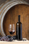 Red wine bottle, cup and grapes on barrels background. — Stock Photo