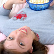 Beautiful young caucasian woman enjoying eating popcorn on her bed. — Stock Photo