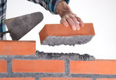 Constructor hand holding a brick and building a wall. — Stock Photo