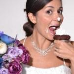 Funny bride eating cake. — Stock Photo