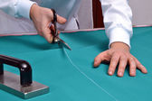 Cutting fabric with a taylor scissors — 图库照片