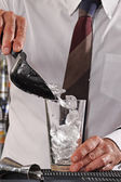 Barman pouring ice cubes on cocktail glass — Stock Photo