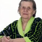 The elderly woman writes to writing-books — Stock Photo