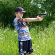 The boy shoots from a pistol — Stock Photo