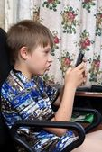 The child plays games on the mobile phone — Stock Photo