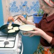 Stock Photo: An elderly woman fry pancakes
