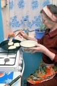 An elderly woman fry pancakes — Stock Photo