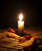 Candle with autumn leaves in night — Stock Photo