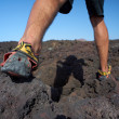 Close-up of man's feet walking on lava field in sport shoes — Stock Photo