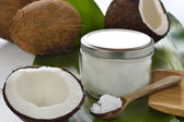 Coconuts and organic coconut oil in a glass jar. — Foto de Stock