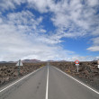 Stock Photo: Straight road through volcanic field.
