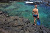 Jeune homme avec des équipements de plongée sur la côte de la roche — Photo