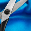 Royalty-Free Stock Photo: A scissors on blue silk