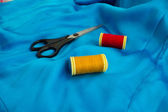 Sewing thread and scissors on silk — Stock Photo