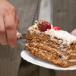 Man puts a cake on a plate — Stock Photo