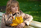A woman with autumn leaves in her hands — Stock Photo