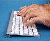 A man writes on PC keyboard — Stock Photo