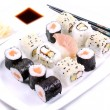 Sushi on a white plate with chopsticks — Stock Photo