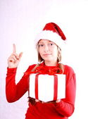 Blond girl as Mrs. Santa gives a present — Stock Photo