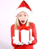 Surprised, young girl as Mrs. Santa with a gift — Stockfoto