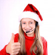 Blond girl as Mrs. Santa with a headset doing ok — Stock Photo #14857493