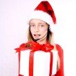 Mrs. Santa speaks with headset and give a gift — Stock Photo #14859075