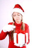 Mrs. Santa holding a gift desperately — Stock Photo