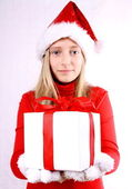 Young girl as Mrs. Santa gives a gift — Stockfoto