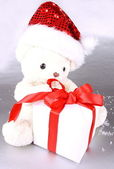 White teddy bear in Santa hat with gift — Stock Photo