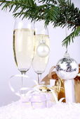Silver New Year's ball on a Christmas tree branch with gifts and champagne — Stock Photo