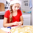 Girl in Santa hat makes cookies from dough — Stock Photo