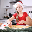 A girl in Santa hat makes cookies from dough — Stock Photo