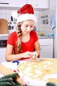 Menina com chapéu de Papai Noel faz bolinhos de massa de pão — Fotografia Stock