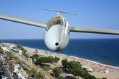 White sailplane flying over sea coast frontal — Stock Photo