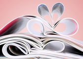 Romantic heart of magazines on a red background — Stock Photo