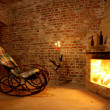 Stock Photo: Rocking chair by fireplace in brick room