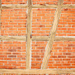 Old red brick wall with wooden beams as background — Stock Photo #18862853