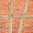 Old red brick wall with wooden beams as background — Stock Photo