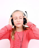 Blond girl listening to music with headphones and is looking forward — Stock Photo