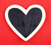 Deska ve tvaru srdce na červeném pozadí zprávy — Stock fotografie