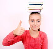 Self-confident girl with OK signand books on head — Stock Photo