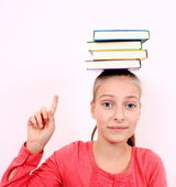 Happy girl with books on head and forefinger — Stock Photo