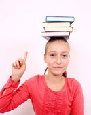 Happy girl with forefinger and books on head — Stock Photo