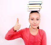 Funny girl with ok sign and books on head — Stock Photo