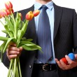 Businessman with bouquet of tulips and two eggs — Stock Photo