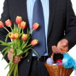 Businessman with tulips and wicker basket full of Easter eggs — Stock Photo
